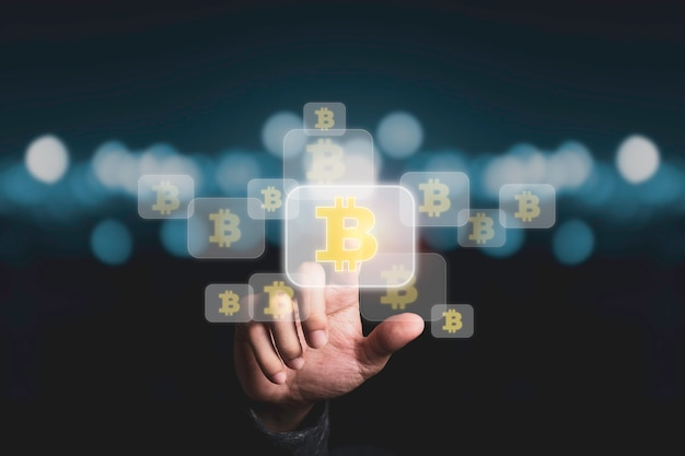 블루 bokeh와 bitcoins 기호를 만지는 손.