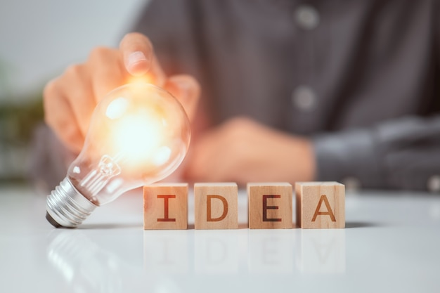 Hand touching on light bulb on wood block with word idea innovative technology in science