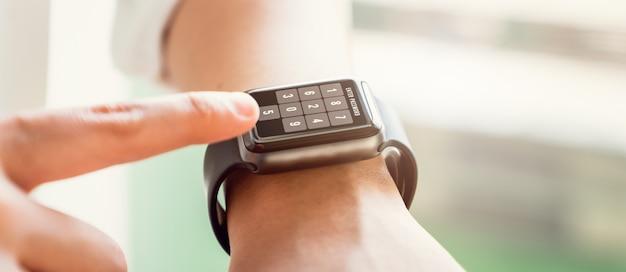 Hand touching password screen on smartwatch to unlock.
