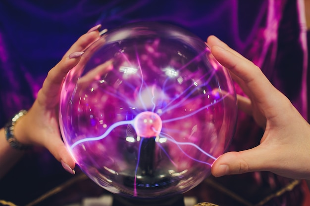 Hand touching plasmball with smooth magenta-blue flames.