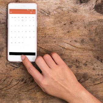 木製のテーブルでスマートフォンに触れる手