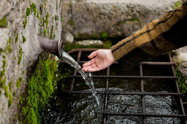 Hand touching water from a natural fountain