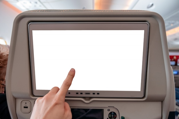 Hand touching on white display screen with joystick on rear seat in airplane