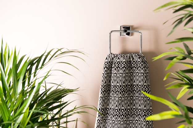 Hand towel with detailed black and white design hanging from a holder on a wall