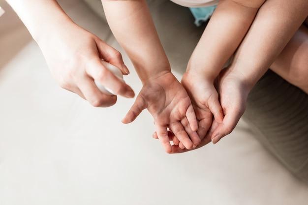 Обработка рук аэрозольным антисептиком. женщина очищает руки ребенка от бактерий и вирусов. детское здравоохранение