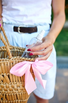 Hand of trendy woman in with straw bag with disinfecting hands gel in handbag