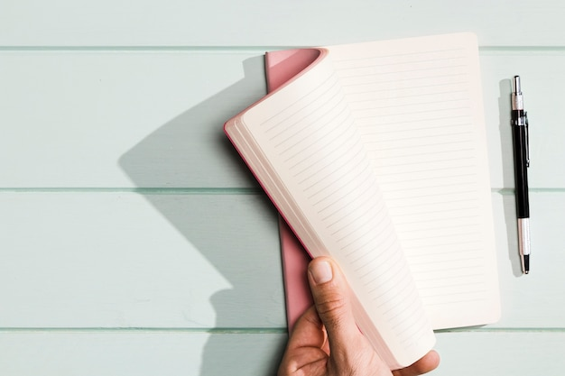 Hand turning the notebook pages with pink covers