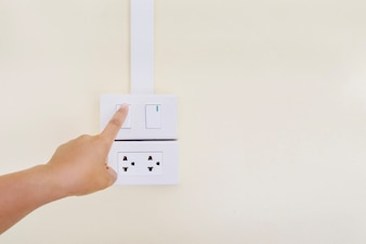 Hand turning on or off light switch