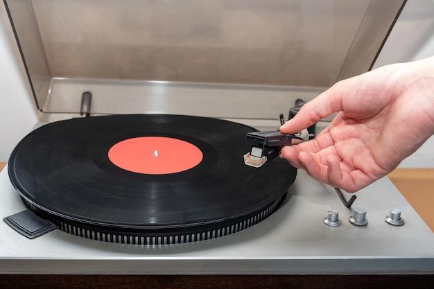 ステレオターンテーブルアナログレトロヴィンテージを手でオンにします。音楽トラックを再生する昔ながらのプラスチック製ターンテーブル、正面図。レトロな音楽のコンセプト