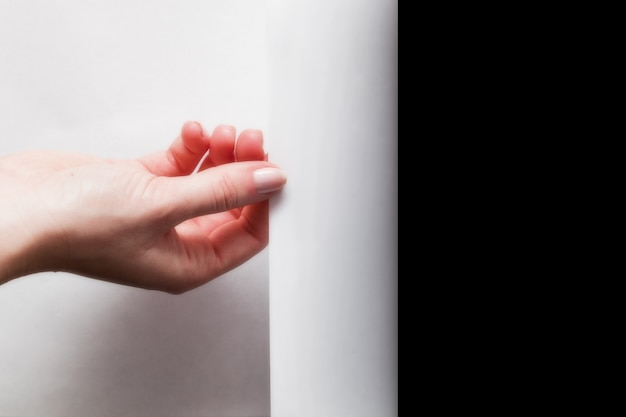 Рука поворачивая белую бумагу
