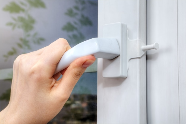 Hand turns the handle of plastic window on which opening limiter is installed.