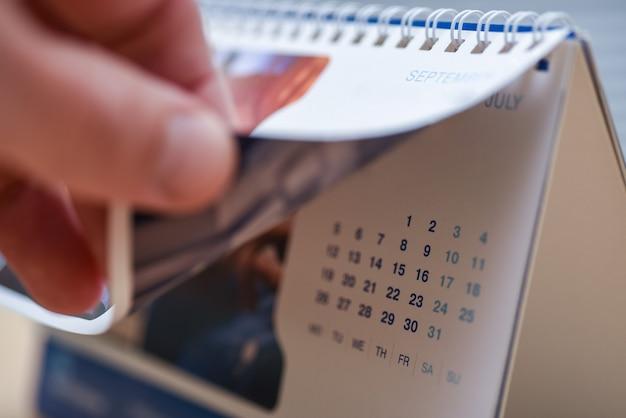 手が卓上カレンダーのページをめくります。
