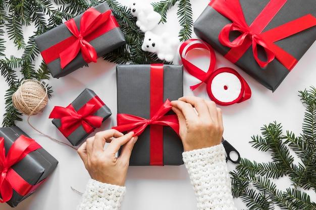 手の小枝の近くのプレゼントボックスに手を結ぶリボン