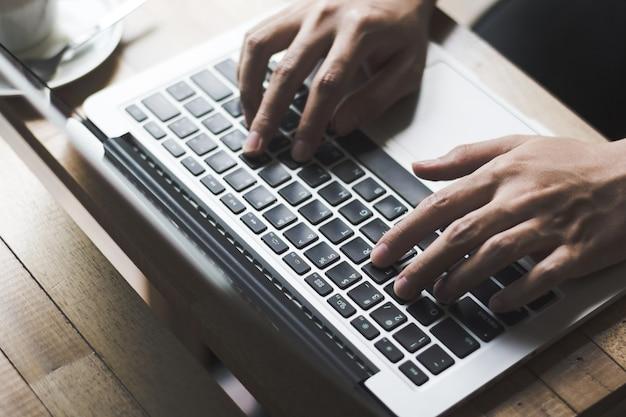 コーヒーショップで木製のテーブルに手を入力するキーボード