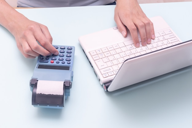 Hand typing on a laptop and a cash register on a blue background. sales person entering amount on cash register in retail store. online e-commerce shopping interface concept.