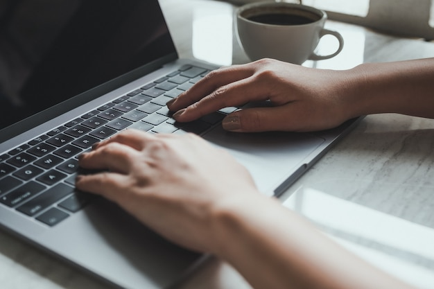 Hand typing on laptop keyboard with coffee cup