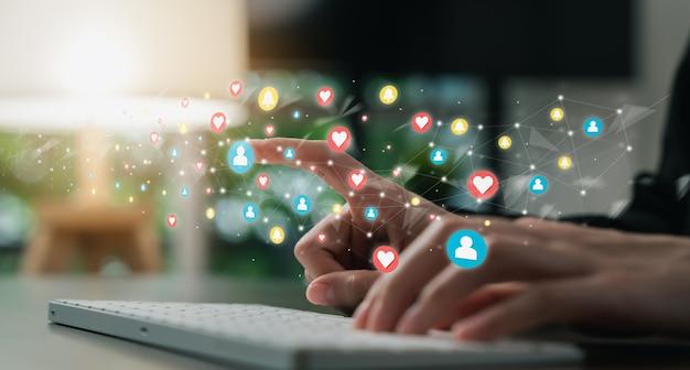 디지털 혁신 및 기술에 대한 소셜 미디어 아이콘이 있는 키보드에 손으로 입력합니다.