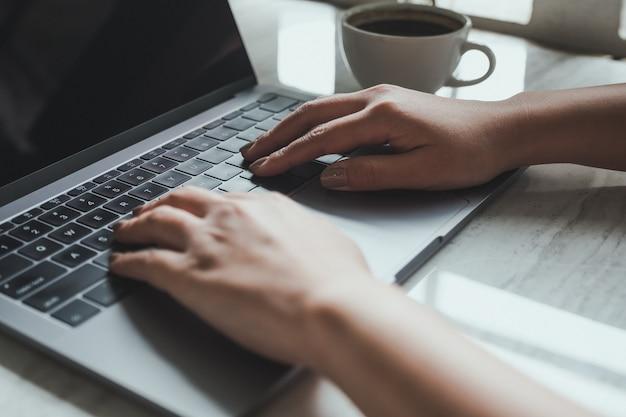 コーヒーカップとノートパソコンのキーボードで入力する手