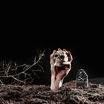 Hand of undead holding skull at dark graveyard on halloween night