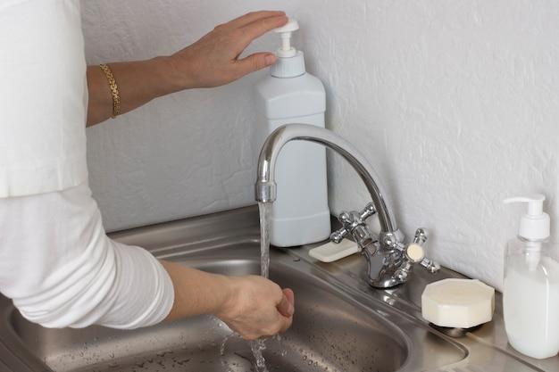 수도꼭지에서 물속에 손을 대십시오. 세제 디스펜서에서 손으로 비누를 사용하십시오. 금속 싱크대에 비누와 디스펜서. 개인 위생.