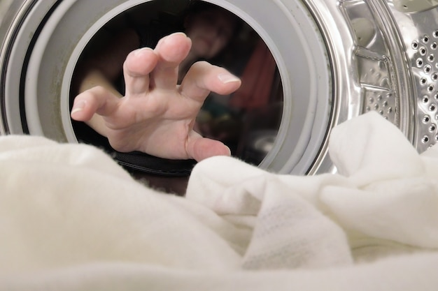 Hand unknown woman puts the laundry in the washing machine