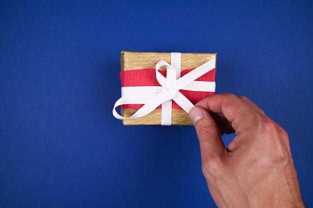 Рука распаковывает крупный план новогоднего подарка.