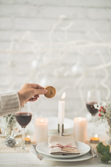 Hand of unrecognizable woman holding cookie above christmas dinner table