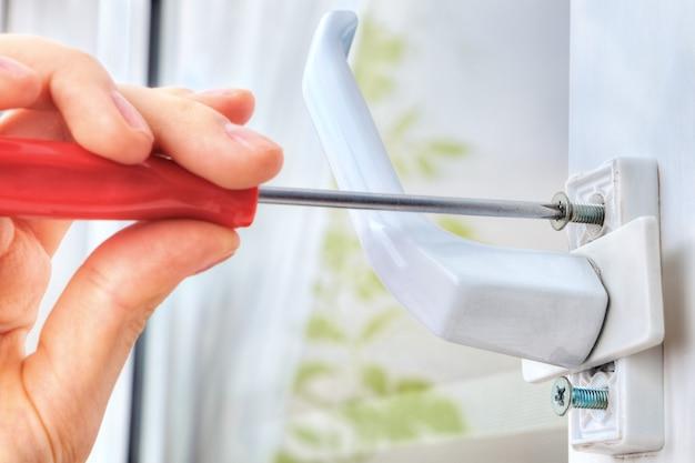 Hand unscrews  bolt, using  screwdriver, dismantling window handle.