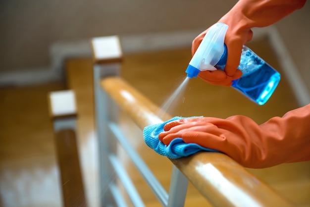 木製の手すり、消毒剤、清潔さとヘルスケアをきれいにするために、ウェットスプレーと布を手で使ってください
