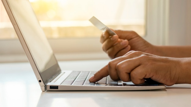 Hand use laptop to shop online and transfer credit card money online banking concept.