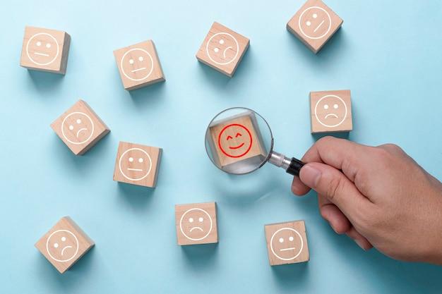 拡大鏡ガラスを手で使って、悲しみと定期的な気分の間の幸せの感情を見つけます。サービスまたはマーケティング調査の後の顧客満足度と評価。