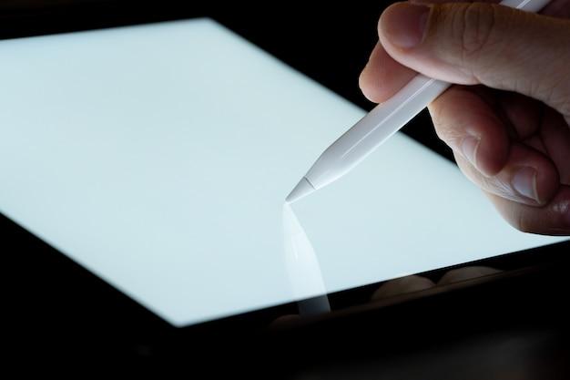 Рука использовать перо стилус сенсорный и дроу на экране планшета с подсветкой. концепция технологии мобильного телефона и будущего взгляда.