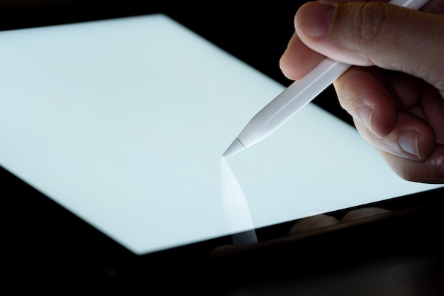 Hand use  pen stylus touch and drow on tablet screen  with light. concept for mobile phone technology and future look.