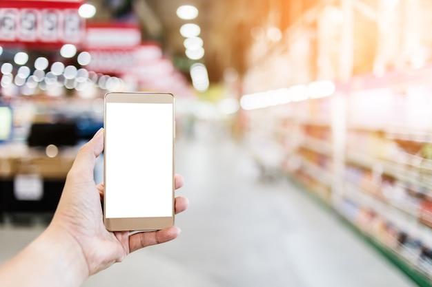 슈퍼마켓의 흐림 배경으로 손 사용 스마트 폰