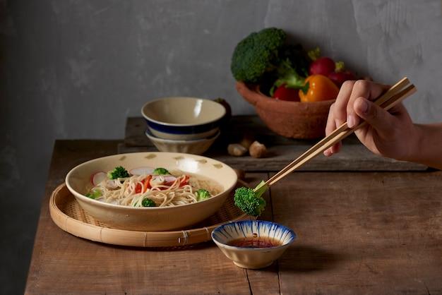 Рука использует палочки для еды, чтобы собрать вкусную брокколи