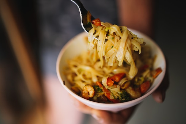 Hand uses fork to pickup tasty noodles with vegetables and shrimp