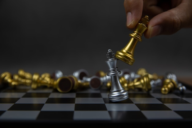 Рука, использующая король шахмат золотого цвета, убивает король шахмат серебряного цвета.