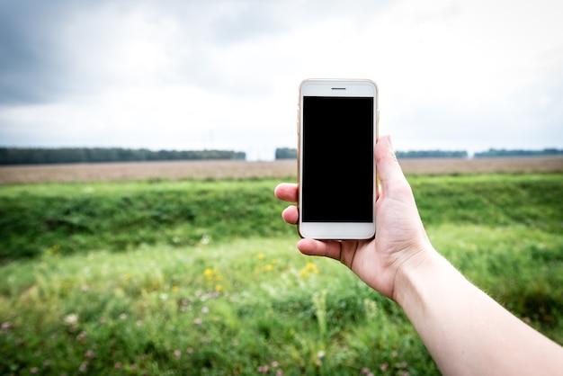 草の上で電話を使用して手