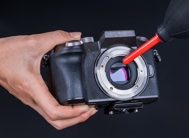 Hand using air blower to cleaning dust on camera sensor