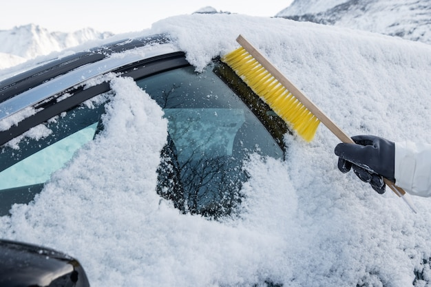 Hand using brush sweeping snow on car windscreen