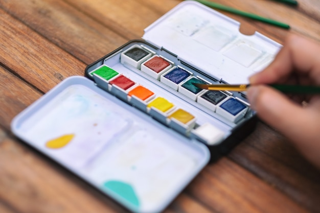 A hand using a brush and watercolor palette for painting