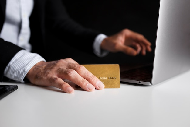 Hand using a card to buy online with laptop