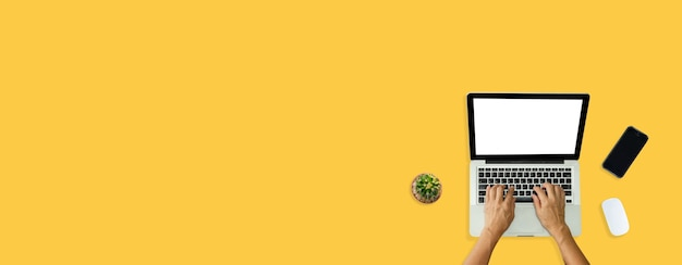 Рука с помощью компьютерного ноутбука и мыши, телефон сверху на желтом фоне.