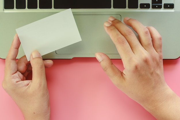 Hand using computer laptop and holding blank business cards on pink background