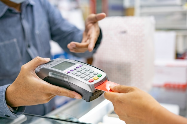 Hand using credit card swiping machine to pay