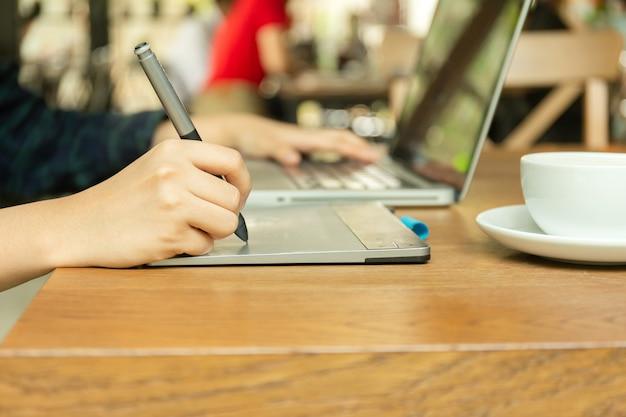 Рука используя цифровую таблетку и penand грифеля работая с портативным компьютером.