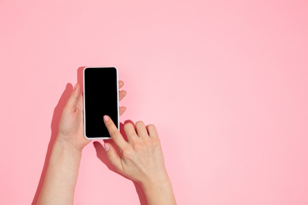Рука с помощью гаджета, смартфон на розовом фоне, вид сверху, пустой экран с copyspace, минималистичный стиль. технологии, модерн, маркетинг.
