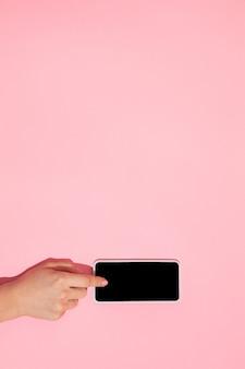 Рука с помощью гаджета, смартфон на виде сверху, пустой экран с copyspace, минималистичный стиль. технологии, модерн, маркетинг. негативное пространство для рекламы. коралловый цвет на стене. стильно, модно.