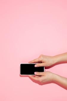 Рука с гаджетом, смартфон сверху, пустой экран с copyspace, минималистичный стиль