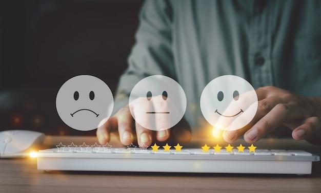 경험 고객 설문 조사의 서비스 평가 피드백을 위해 해피 아이콘 및 별 5개가 있는 키보드를 사용하여 손을 사용합니다. 비즈니스 연간 만족도 개념입니다. 많은 슬프거나 행복한 아이콘, 우수한 성능.